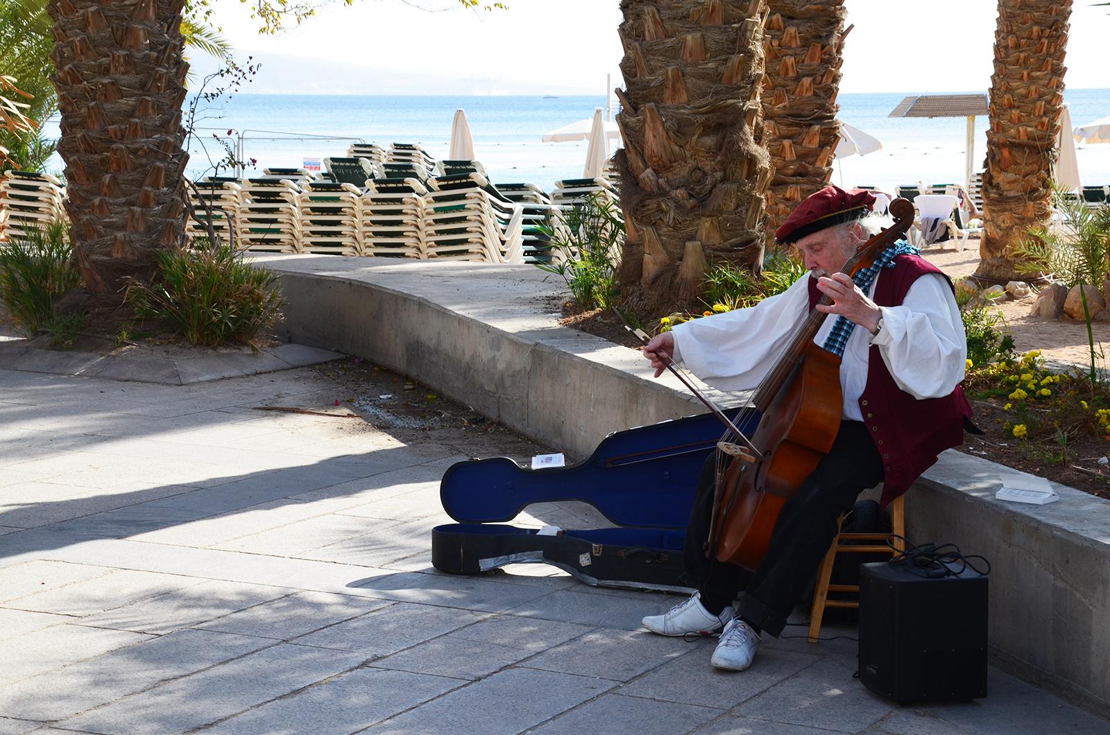 gambista hrající kolemjdoucím na promenádě v Eilatu