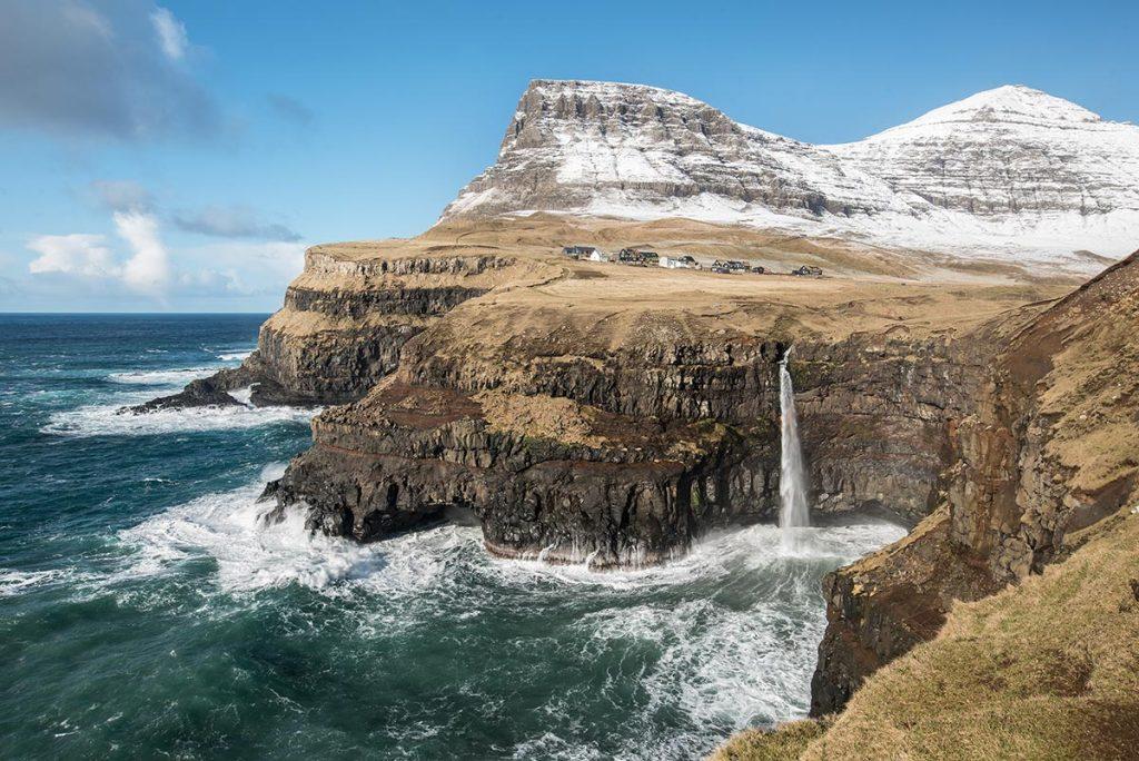 Vodopád Múlafossur u vísky Gásadalur na Faerských Ostrovech. A se sněhem pocukrovanými vrcholkami na pozadí